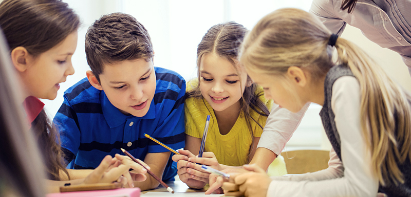 education, elementary school, learning and people concept - teacher helping school kids writing test in classroom Image ID:306948110 Copyright: Syda Productions Release Information: Signed model release filed with Shutterstock, Inc